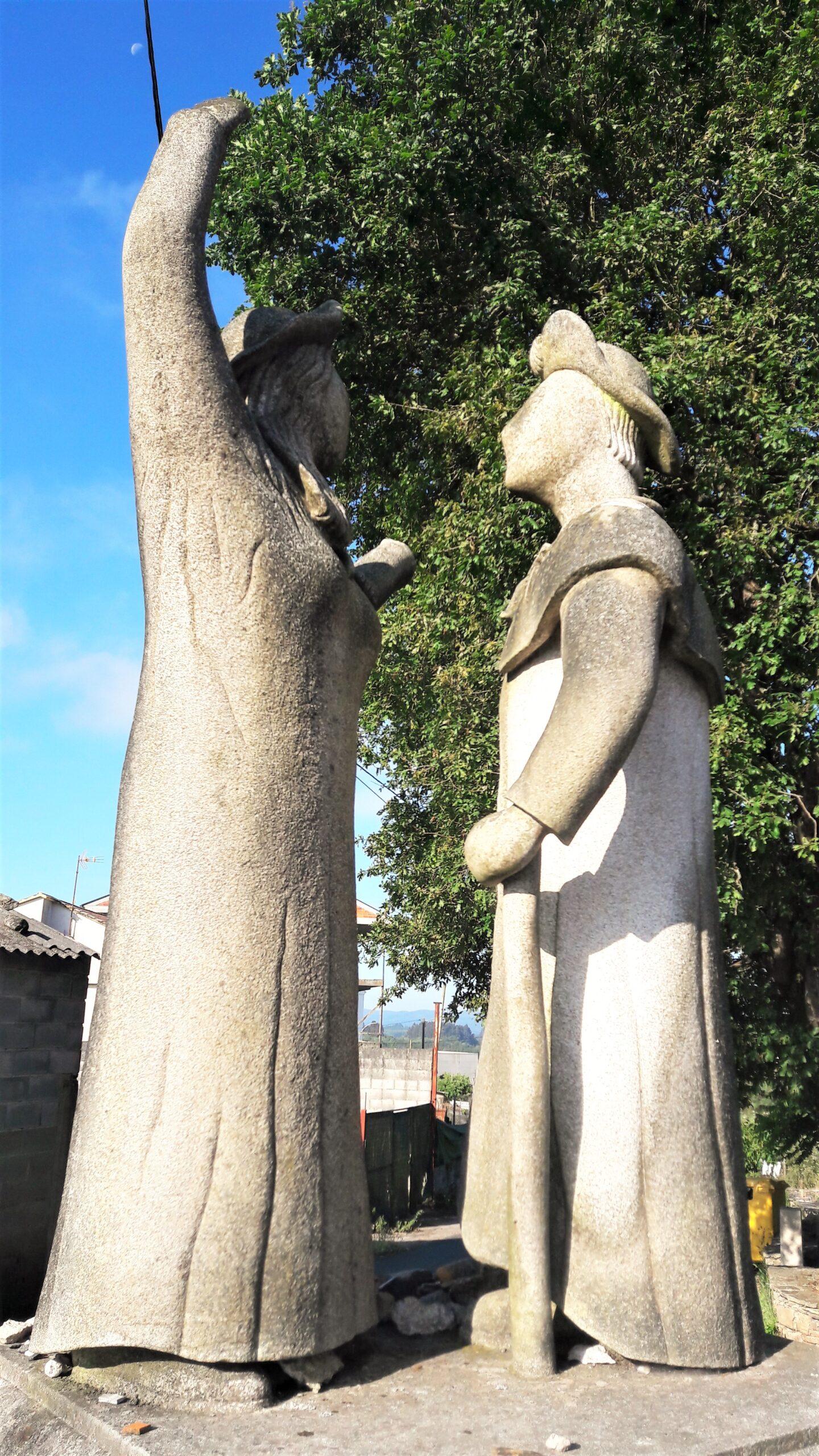 Kunstwerk van twee pelgrimsbeelden. De ene wijst, de andere luistert.
