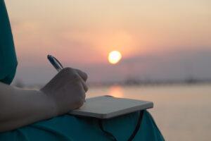 schrijvende persoon bij zonsondergang