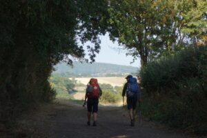 Twee pelgrims op pad met bomen lopen richting zonnig dal