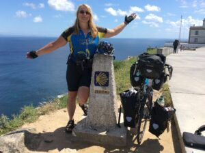 Bicigrina met haar fiets bij een caminomijlpaal aan de kust