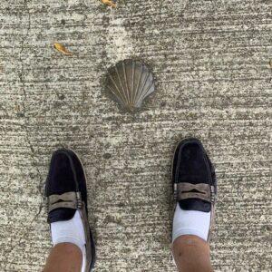 twee voeten in instappers bij een metalen Jacobsschelp in het plaveisel