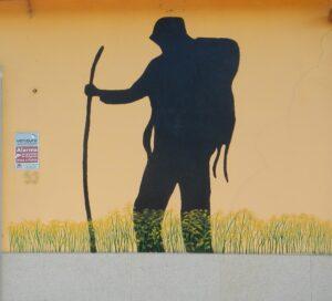 silhouet van persoon met rugzak op een zonnige gele muur