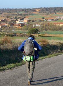 Pelgrim op de rug gezien met uitzicht op een dorp in de verte