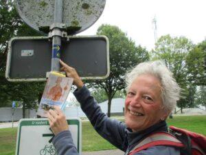 Blijde wandelaar met gids caminoroutes in Nederland bij een paal met een caminosticker